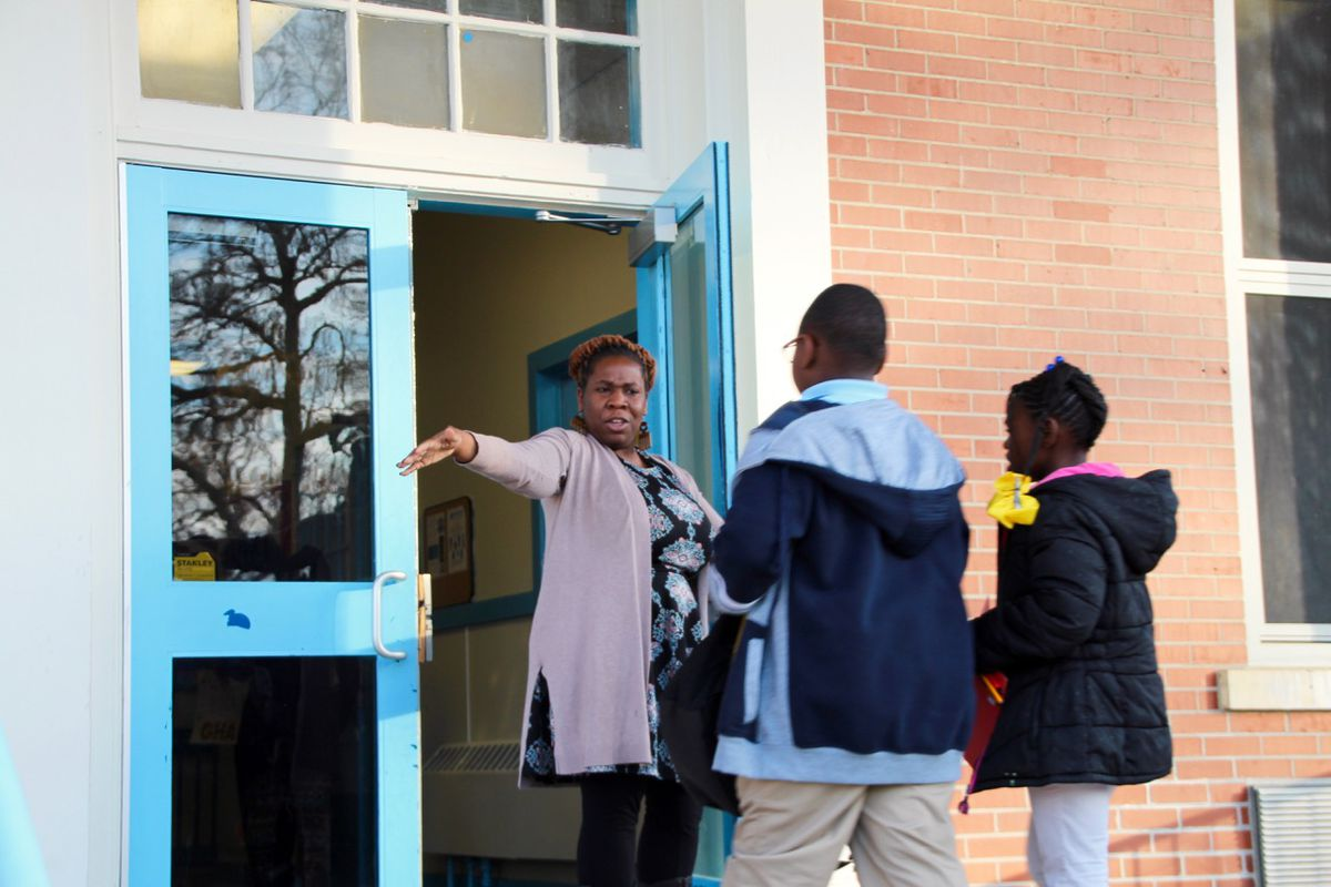 Teacher support coach Deborah O'Neil welcomes students with hugs as they return to classes.