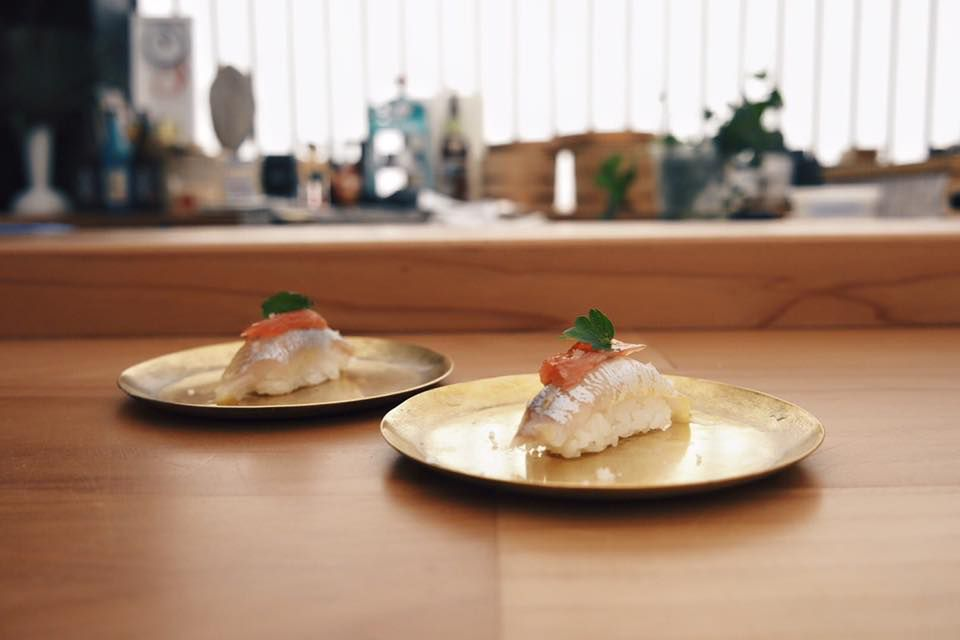 Two circularly plates each with a piece of sushi on them.