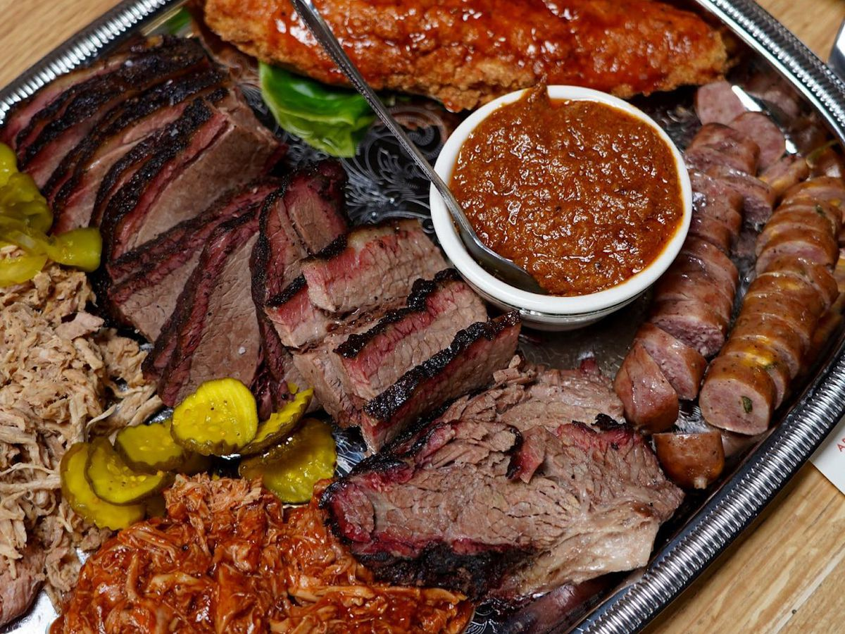 A silver travel is piled high full of brisket, smoked pork, ribs, smoked sausage, Brunswick stew, and smoked chicken from Buxton Hall BBQ in Asheville, NC.