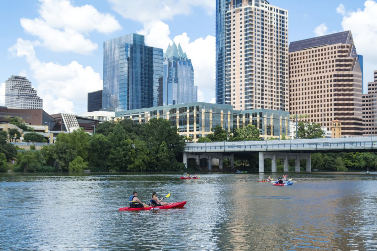People canoeing on Lady Bird Lake in Austin with the Austin skyline in the background