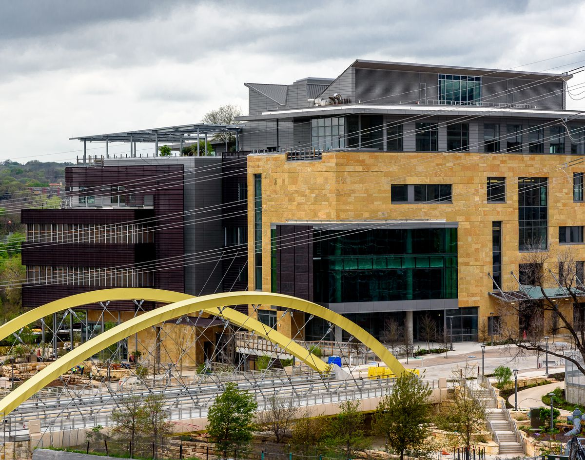 Photo of a six-story limestone, glass, and steel building in a downtown setting with an arched truss bridge for pedestrians in the foreground.