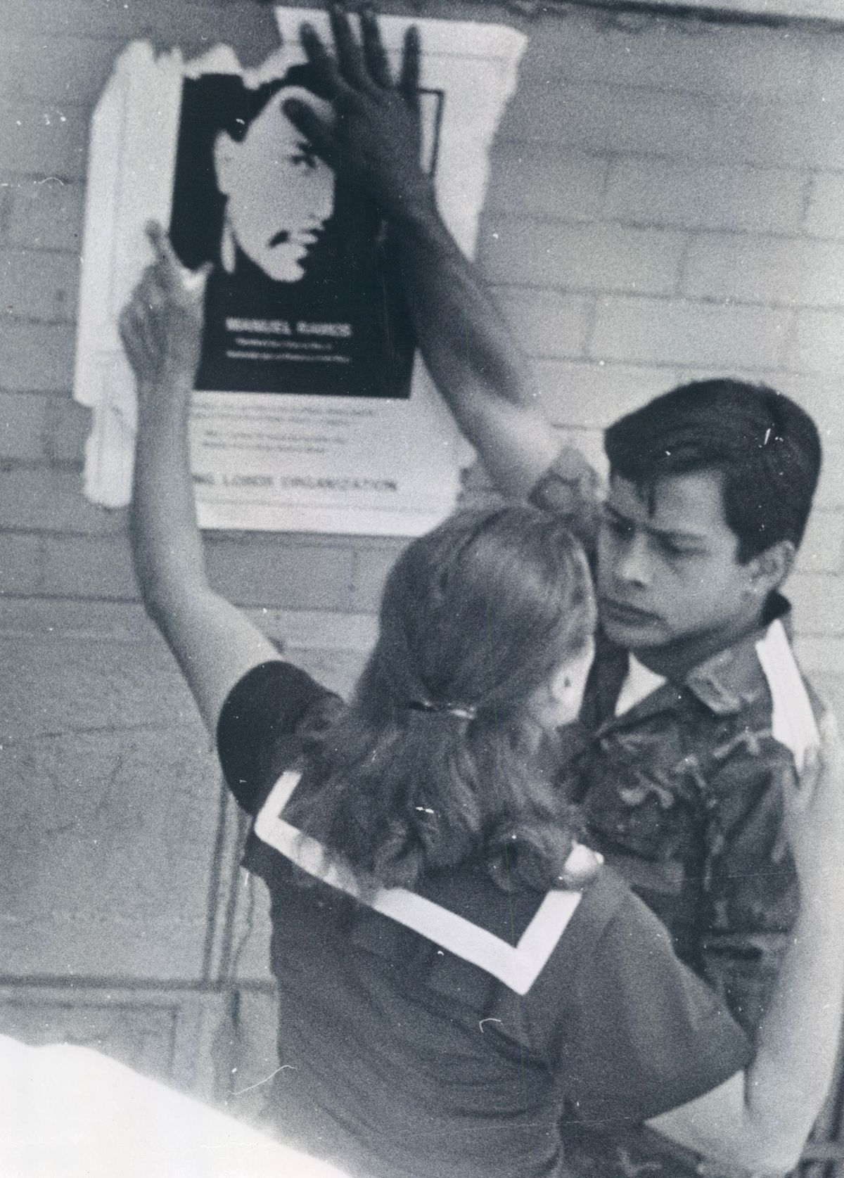 A woman tries to tear down poster of Manuel Ramos, slain Young Lords member, which was on wall of her building in the 800 block of West Armitage Avenue in August 1969.