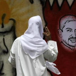 A Bahraini man looks at an image of jailed hunger striker Abdulhadi al-Khawaja painted on a map of Bahrain on a wall in Barbar, Bahrain, west of the capital of Manama, on Monday, April 30, 2012. A defense lawyer says a Bahrain appeals court has ordered the reexamination of the case of al-Khawaja and more than a dozen others.