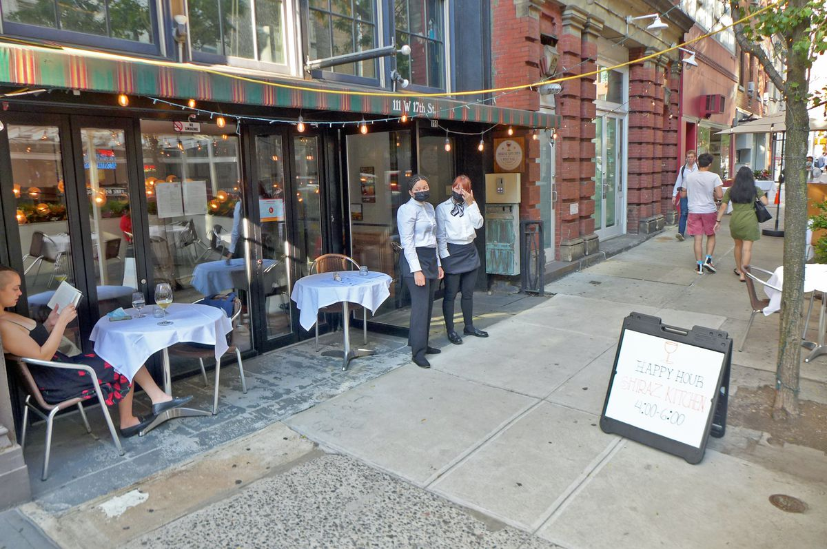 A storefront with a stiped awuing and two aproned servers stand in front with a seated patron reading a book at far left.