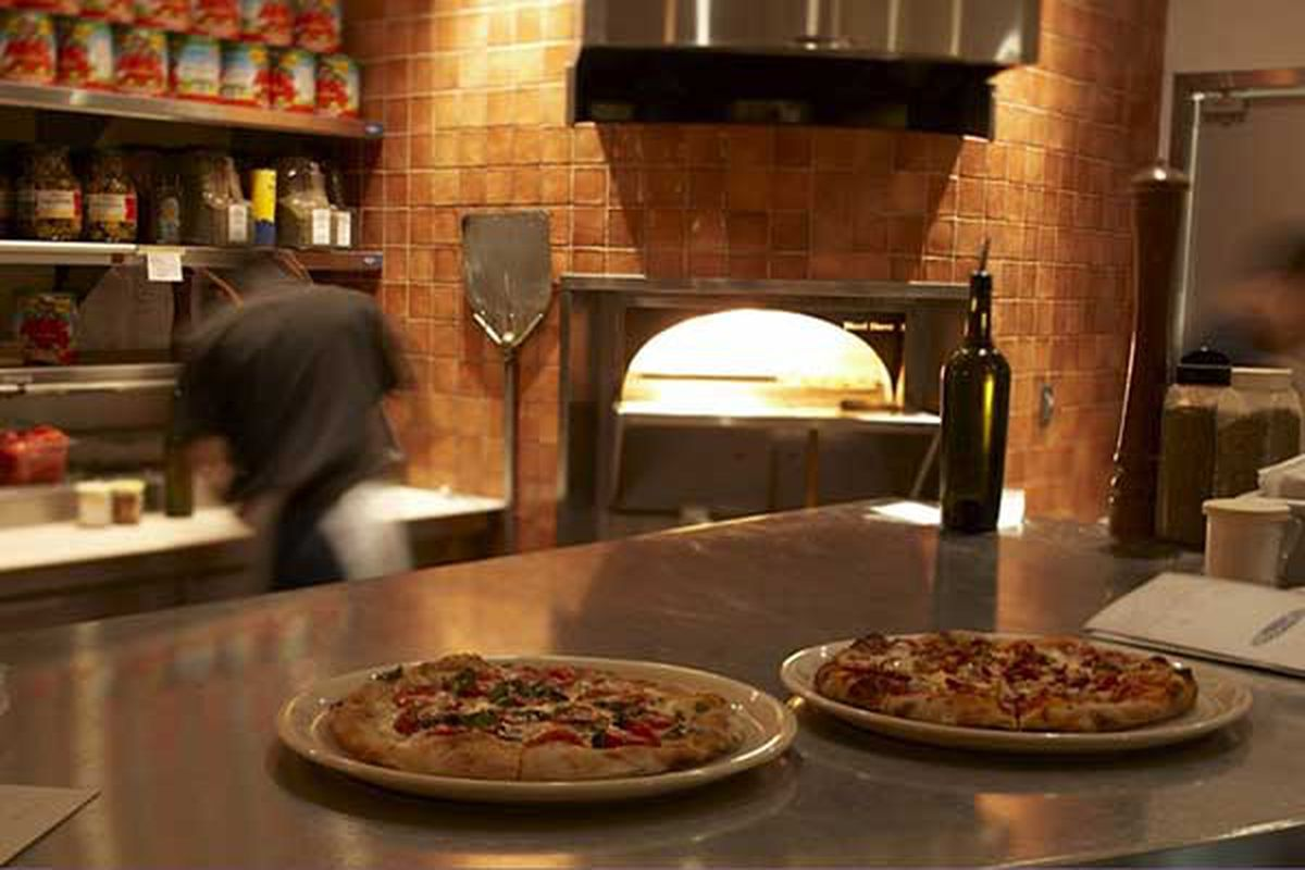 Two pizzas on tin rounds sit on a counter in front of a blazing woodfire stove