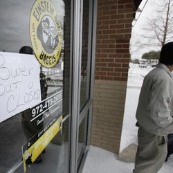 A sign announces a business is closing due to a power outage as Antonio Carreno, left, and Taylor Sticker stand outside in Plano, Texas, Wednesday, Feb. 2, 2011. The cold has forced rolling blackouts across Texas.