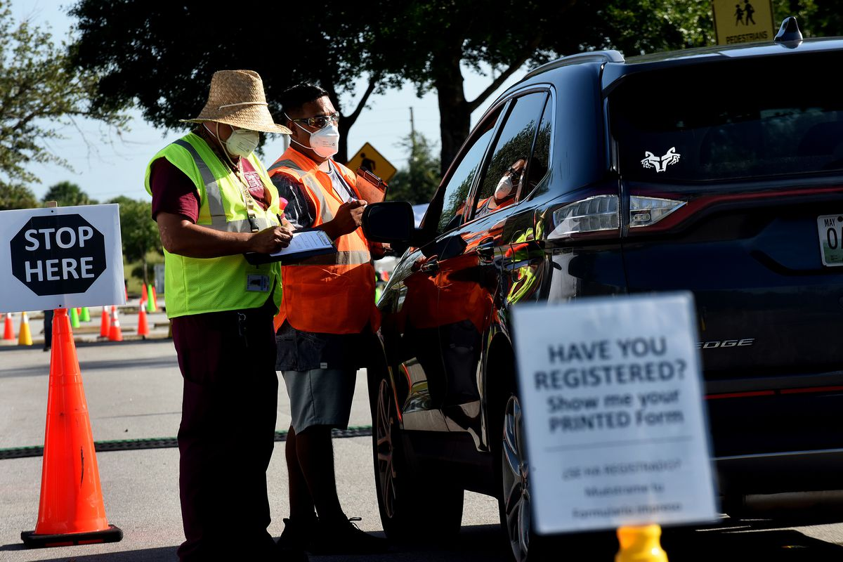 Workers greet people in a car at a nearly empty COVID-19...