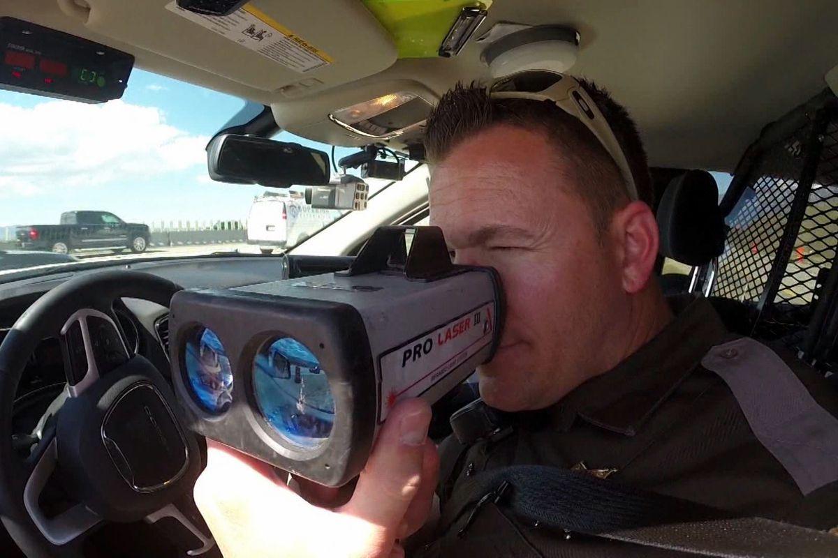 A Utah Highway Patrol trooper uses a radar gun to watch for speeding drivers.