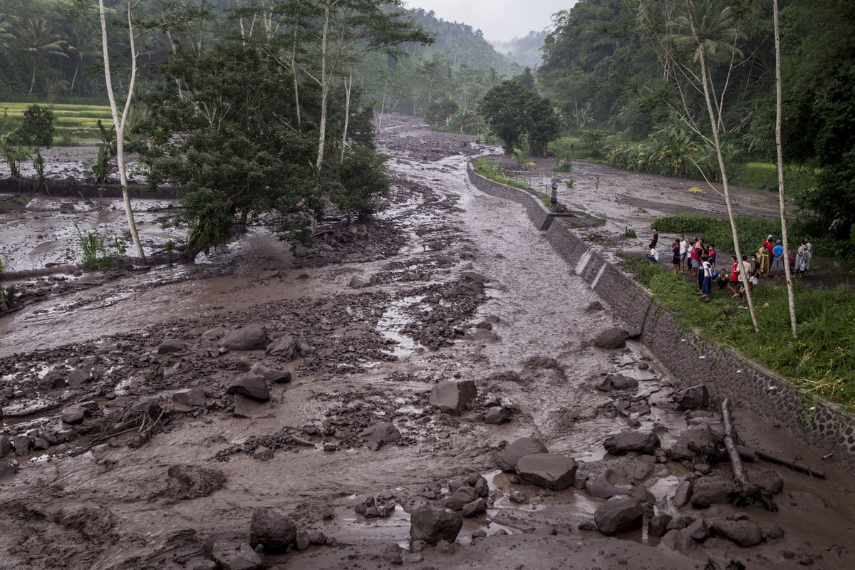KARANGASEM, BALI, INDONESIA - NOVEMBER 27: Volcanic material from Mount Agung flows through a local river in Gesing Village while villagers are seen watching nearby on November 27, 2017 in Karangasem, Island of Bali, Indonesia. Indonesian authorities raised the state of alert to its highest level for the volcano, Mount Agung, after thick ash started shooting thousands of meters into the air with increasing intensity. Based on reports, as many as 100,000 villagers will need to leave the expanded danger zone while tens of thousands of tourists have been stranded due to airport closures. (Photo by Andri Tambunan/Getty Images)