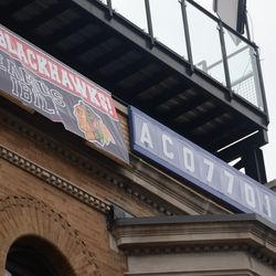 """11:19 a.m. Blackhawks banner at the top of the """"EAMUS CATULI"""" building on Sheffield -"""