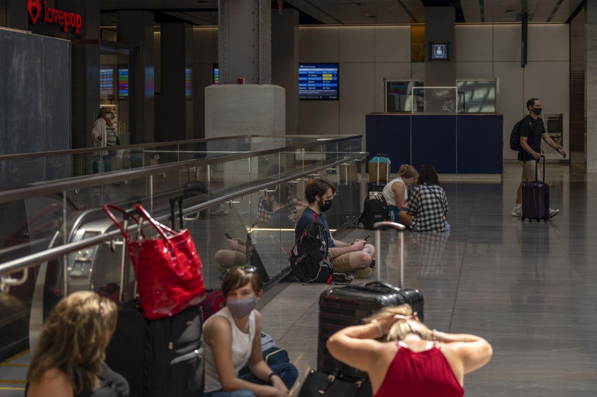 Travelers sitting on the floor in Moynihan Train Hall. Aug. 13, 2021.
