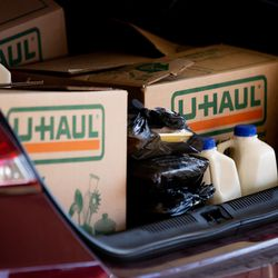 Chicken, milk and boxes of food fill the trunk of a car as people pick upfoodat Calvary Baptist Church in Salt Lake City on Saturday, Dec. 19, 2020.