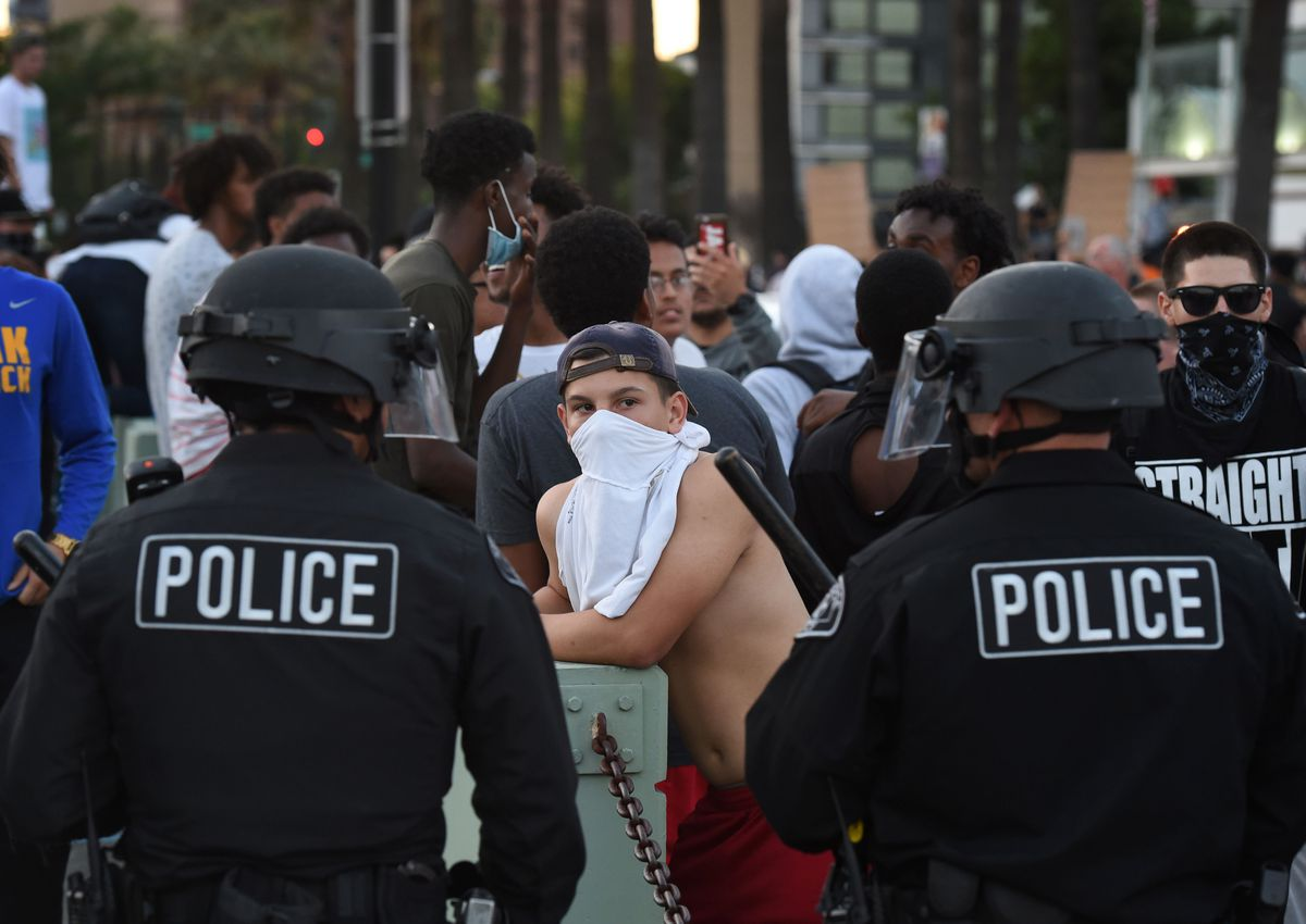 A protester faces off with police outside a Donald Trump rally in San Jose, June 2, 2016.