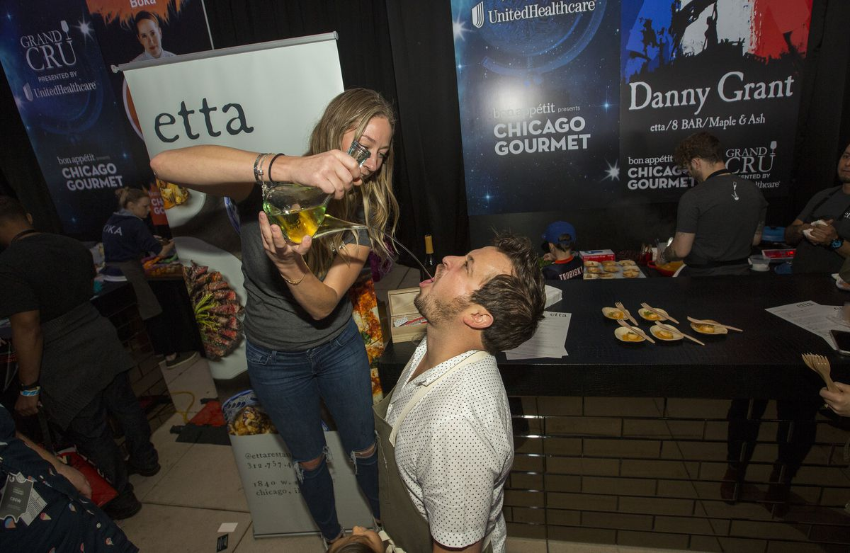 A woman pours alcohol down a kneeled chef's throat.