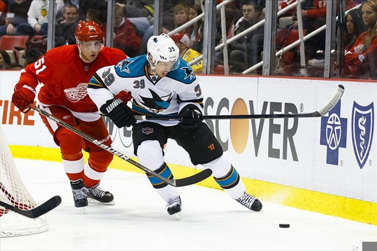 Feb. 19, 2012; Detroit, MI, USA; San Jose Sharks center Logan Couture (39) and Detroit Red Wings center Valtteri Filppula (51) battle for the puck in the second period at Joe Louis Arena. Mandatory Credit: Rick Osentoski-US PRESSWIRE
