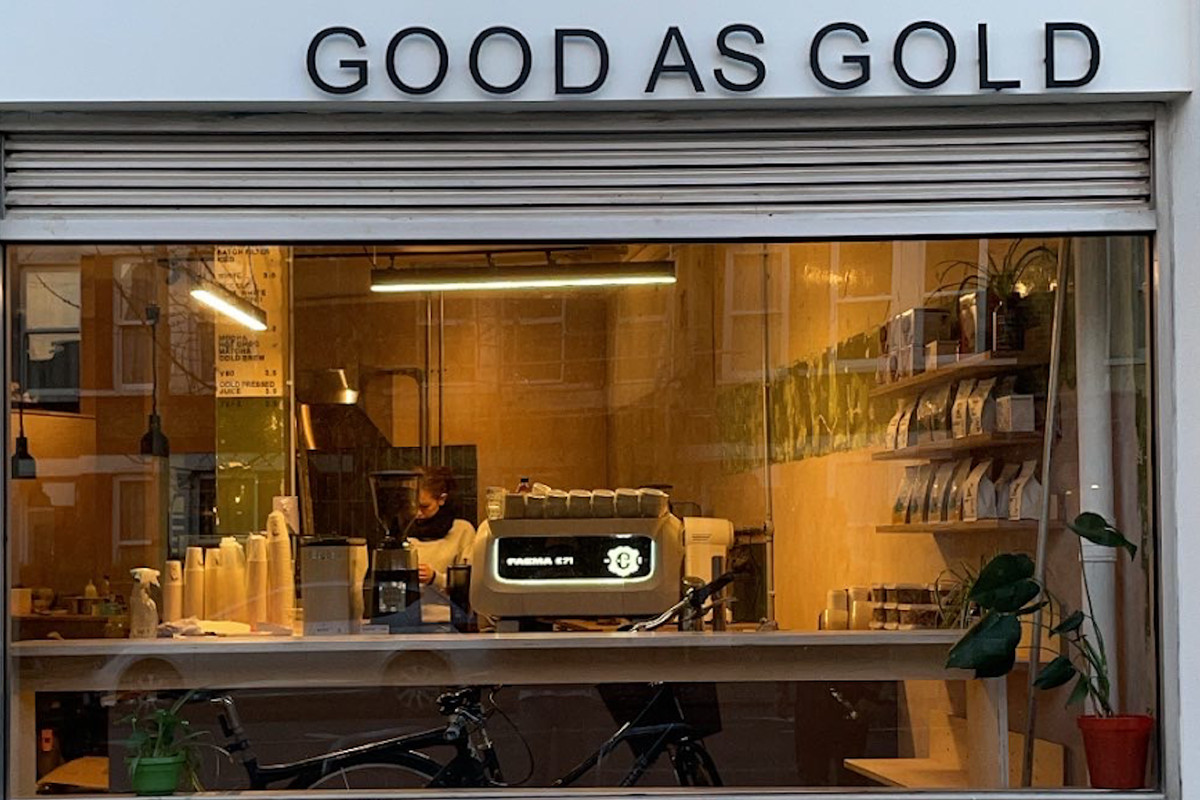 The exterior of Good as Gold cafe in Brockley, with the espresso bar bathed in warm light and the name above the window in all caps
