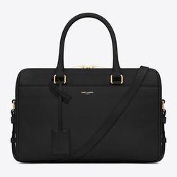 "<strong>Saint Laurent</strong> Classic Duffle 6 Bag, <a href=""http://www.ysl.com/us/shop-product/women/handbags-duffle-6-classic-duffle-6-bag-in-black-leather_cod45204601xc.html"">$1,990</a>"