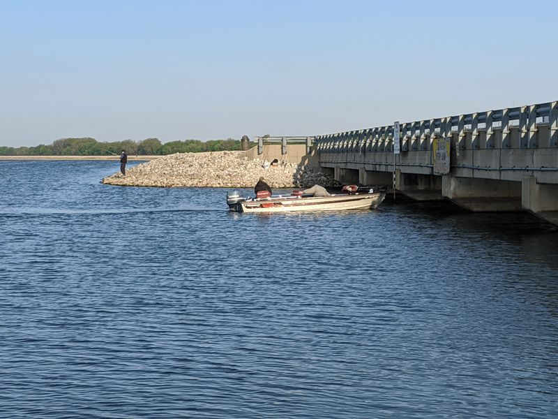 A boater ducked to get under the bridge on the center dike in May last year at Heidecke Lake, which became a packed destination as pandemic closures eased; prospects look good for 2021 at the former cooling lake, which reopens to fishing Thursday. Credit: Dale Bowman