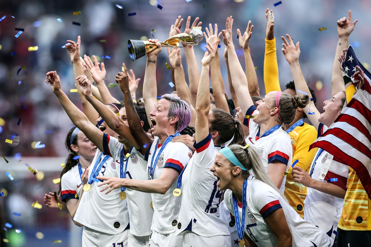 a98bab945 Megan Rapinoe of the USA lifts the FIFA Women's World Cup Trophy,  surrounded by teammates