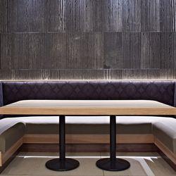 A wraparound booth sits below a beautiful slate wall