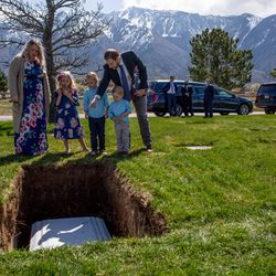 Clarissa Ragar and Evalee Ragar, 7, Decklin Ragar, 5, Wynston Ragar, 3, and Joel Ragar look at where Joel's grandfather is buried next to his wife at Larkin Sunset Gardens in Sandy on Monday, April 20, 2020. The World War II veteran lived in Alpine with his wife before moving to Arizona and passing away after being hospitalized alone for about a month at age 93 during the coronavirus pandemic.