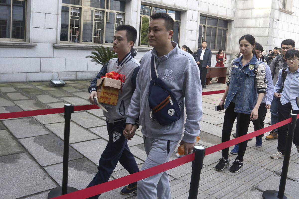 Sun Wenlin, left, and his partner, Hu Mingliang, hold hands as they arrive at the Furong District Court to argue in China's first gay marriage case in Changsha.