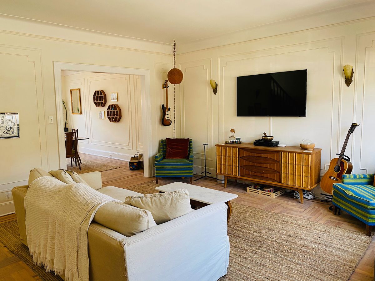 A living area with beige walls, crown and base moldings, a brown rug, and hardwood floors.