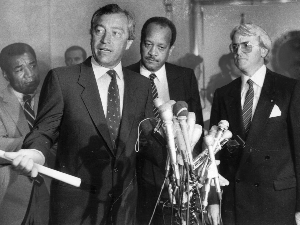 Following the hour-long summit between Mayor Washingrton and leaders of the Vrdolyak 29, Ald Edward R. Vrdolyak (10th) talked to the press in 1984. Watching are (from left) Ald. Wilson Frost (34th), Corporate Counsel James L. Montgomery and Ald. Edward M.