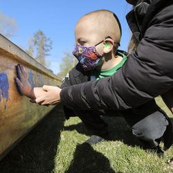 Kahnrad Koontz, a pre-k student at the Utah Schools for the Deaf and the Blind, puts his handprint on All Hands on Deck, a boat built by students and staff,, outside of the Openshaw Education Center in Millcreek on Tuesday, April 20, 2021. The school's yacht club will race the boat the SEVENTY48, a 70-mile human-powered boat race from Tacoma to Port Townsend, Wash.