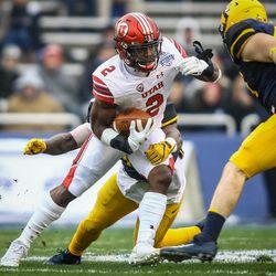 Utah Utes running back Zack Moss (2) escapes the grasp of West Virginia Mountaineers linebacker David Long Jr. (11) at the Zaxby's Heart of Dallas Bowl between the Utah Utes and the West Virginia Mountaineers in Dallas Texas on Tuesday, Dec. 26, 2017.
