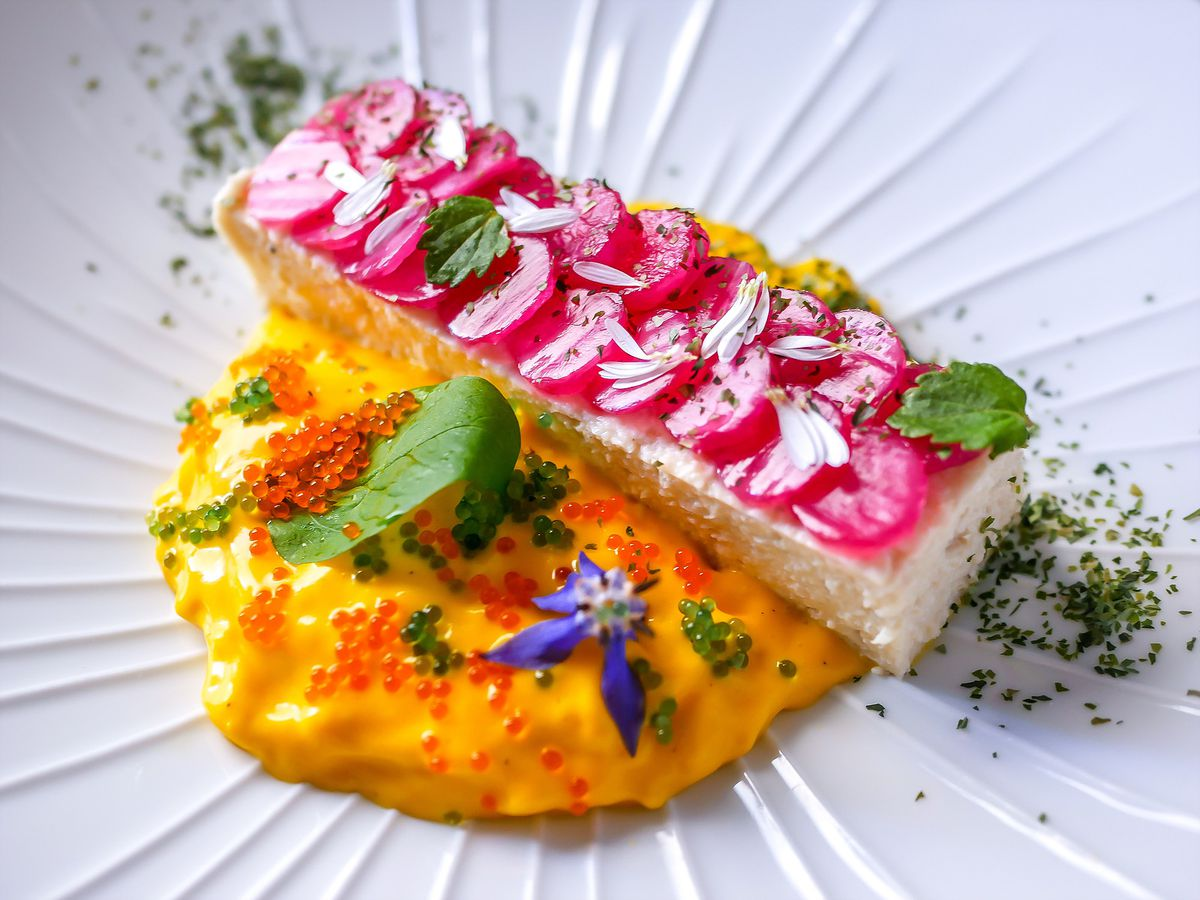 A long rectangular cut of fish topped with medallions of bright vegetables sitting in a bright saffron cream dotted with fixings