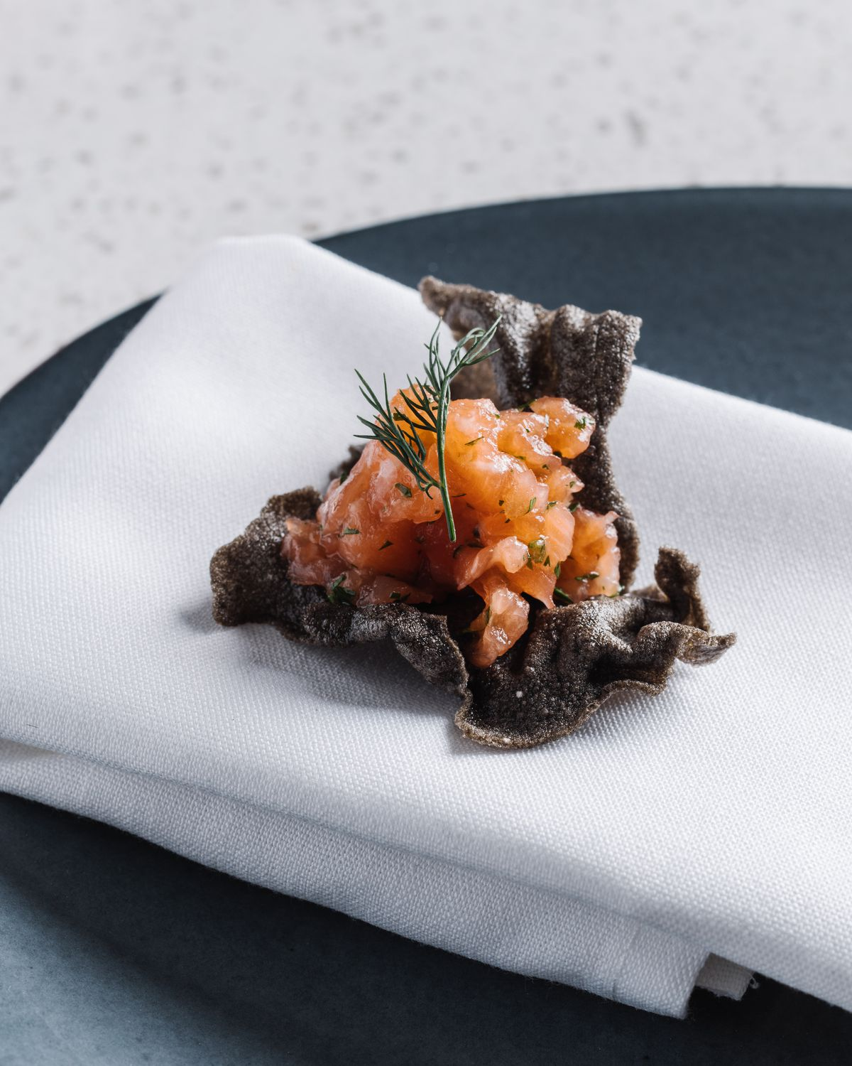 Salmon Tartare with Persian cucumbers & squid ink chip at Lazy Betty