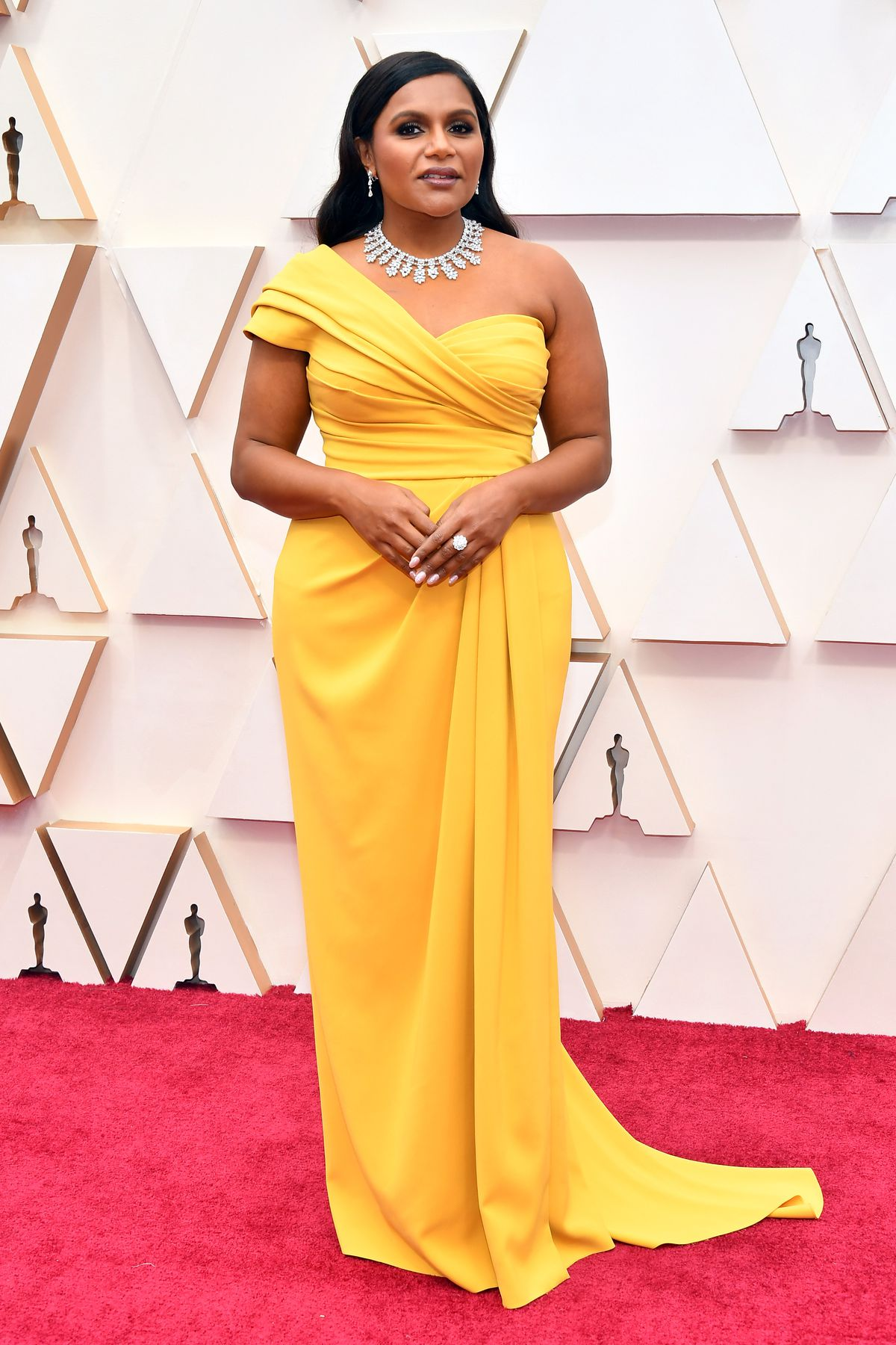 Mindy Kaling attends the 92nd Annual Academy Awards in a yellow Dolce & Gabbana gown.