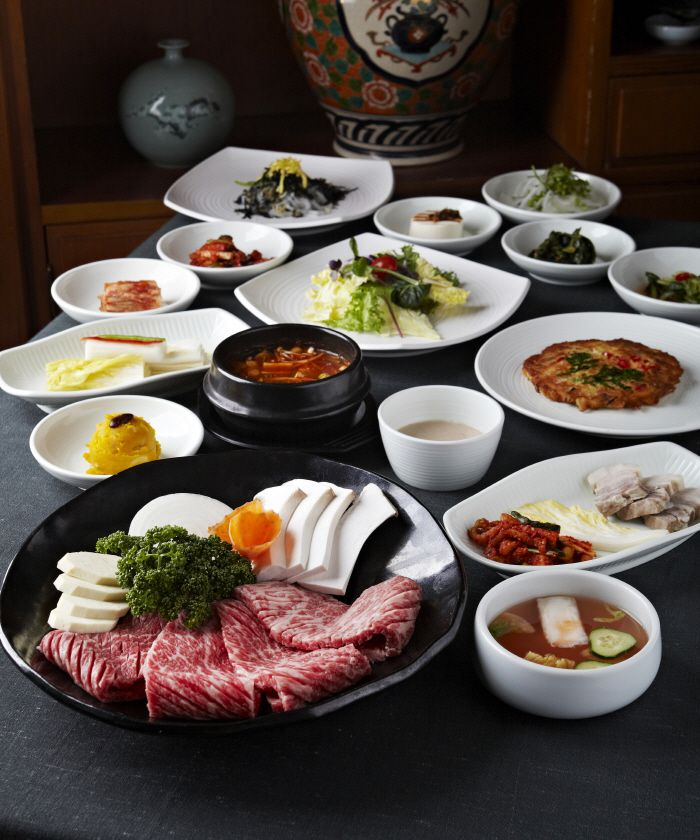 A spread of dishes for Korean barbecue grilling is laid out on a table
