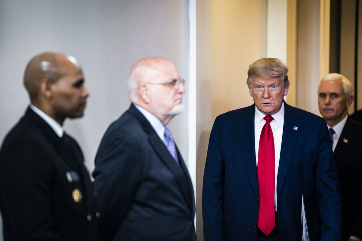 Trump, flanked by Vice President Mike Pence, walks in front of the CDC's Robert Redfield, and US Surgeon General Jerome Adams.