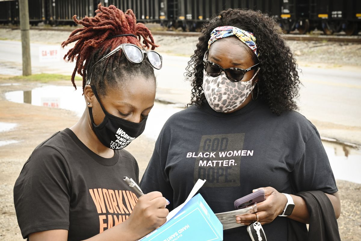 """Two women at a get-out-the-vote event outdoors, both wearing masks. One wears a T-shirt reading, """"Black women matter""""; the other wears one reading """"Working families."""""""