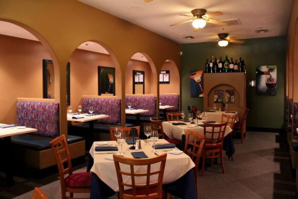 A restaurant with brown walls, purple booths and fans on the ceiling