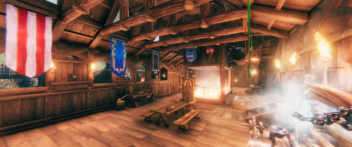 Valheim - an internal shot of a large hall decorated with trophies and colorful banners.