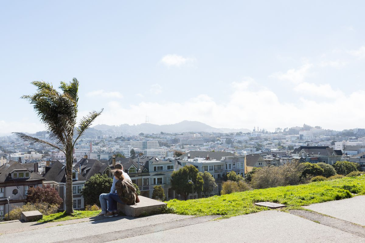 Two people sit on a bench on the side of a cliff overlooking the city of San Francisco.