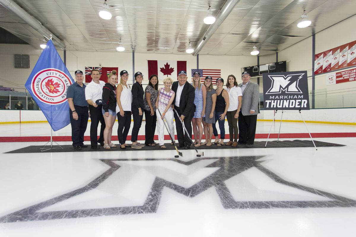 CWHL Commissioner Brenda Andress and Markham Mayor Frank Scarpitti pose with players and staff from the Markham Thunder. A Markham Thunder logo is painted into the ice in front of them.
