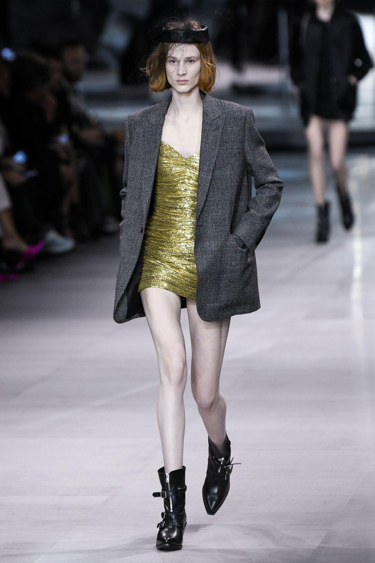 9123a269410e A model wears a gold minidress and a gray blazer. Slimane s Celine ...