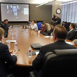Those in attendance listen as U.S. Sen. Mike Lee speaks by video during a roundtable in Cottonwood Heights, Thursday, Nov. 20, 2014, concerning immigration reform.