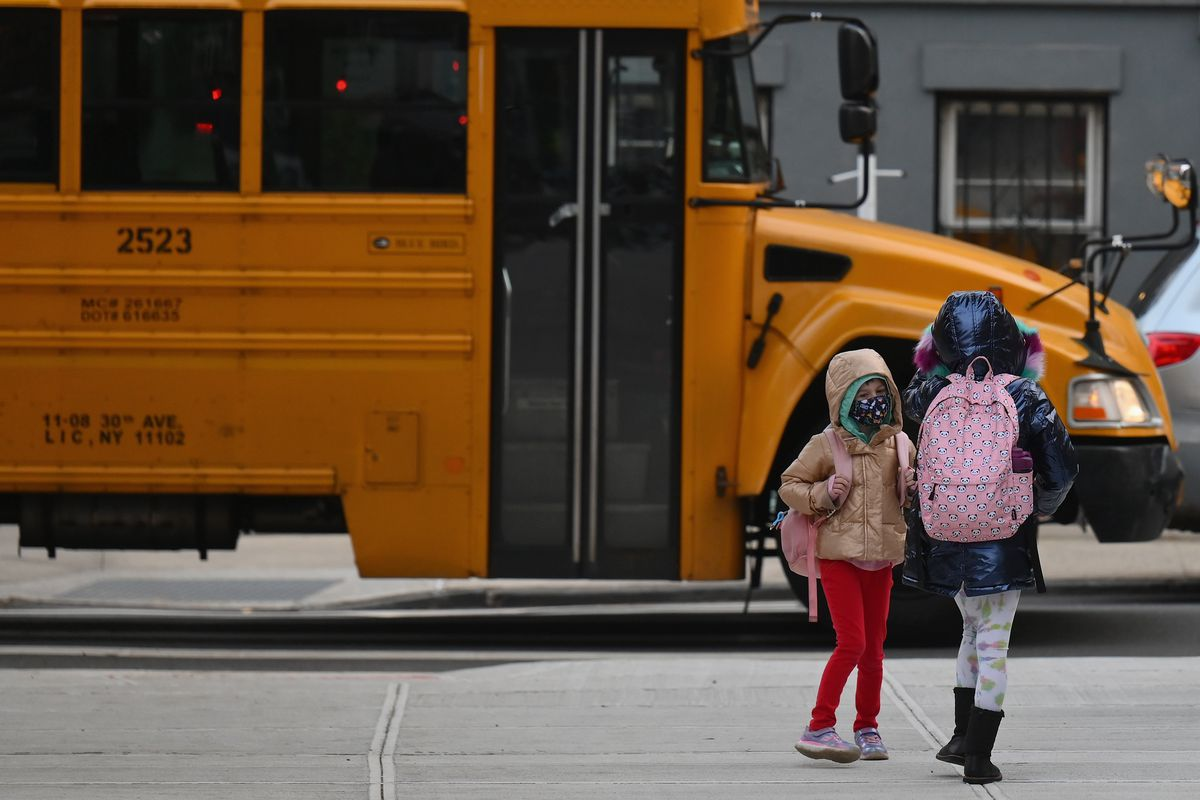 Two children with backpacks, one wearing a mask, the other seen from behind, standing on a sidewalk in front of a school bus.