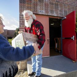 Jill Smith hands Merlin Taylor a box of donations as the 19th annual Candy Cane Corner holiday store prepares to open in the old Granite High School pool building in South Salt Lake on Monday, Nov. 30, 2015.