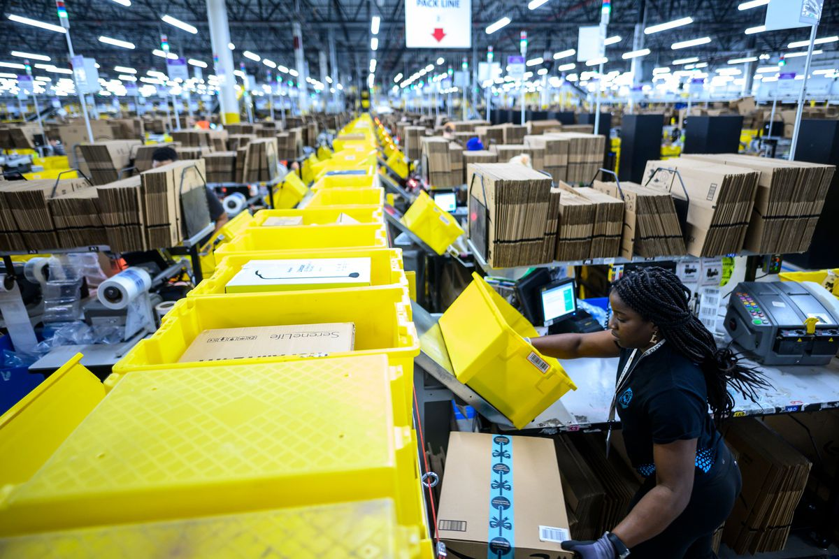A woman works at Amazon's huge packing station warehouse in Staten Island, New York City.