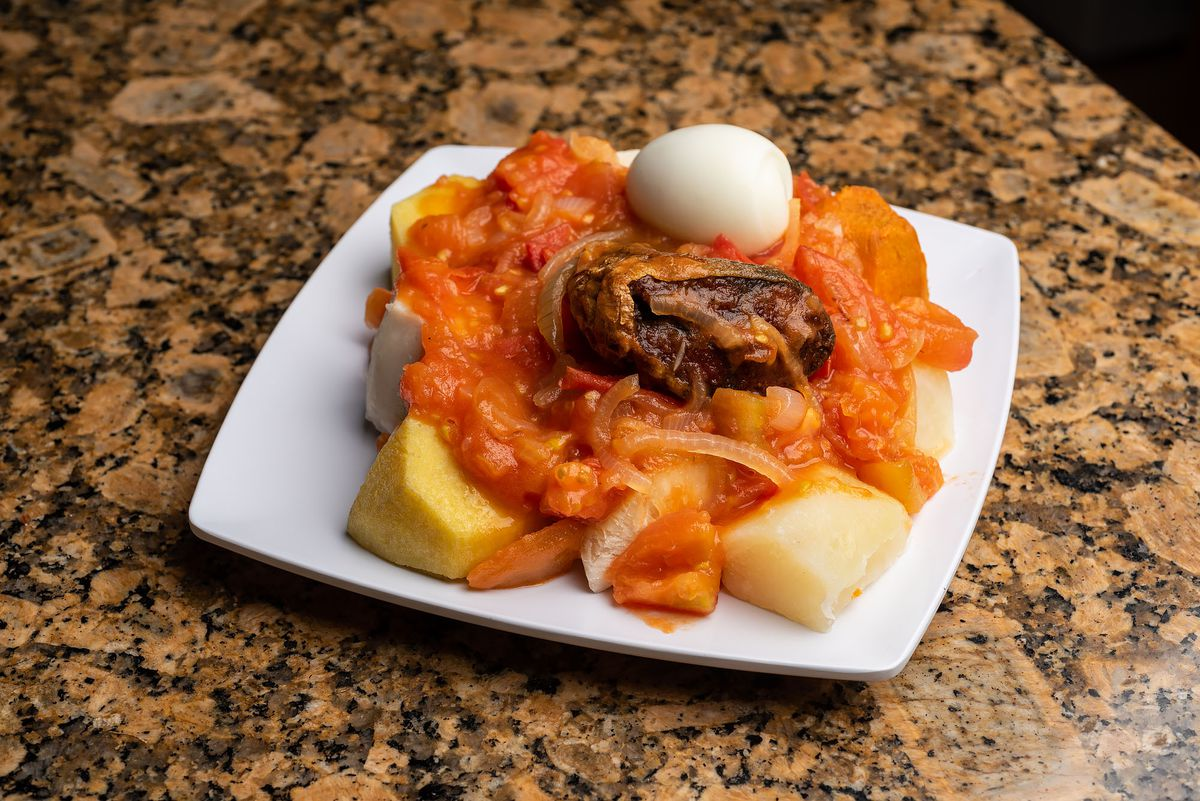 Boil up, a pork-seasoned pot of assorted root vegetables, flour-based boil cakes, pig tail, fish, and hard-boiled egg, with canned tomato sauce
