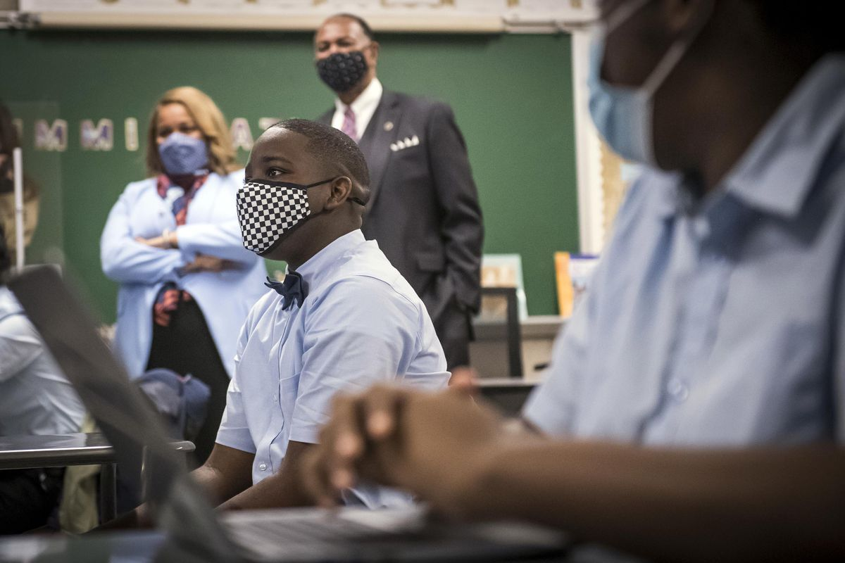 Students in blue shirts and protective masks look toward the front of the classroom as Commissioner Porter observes in the background.