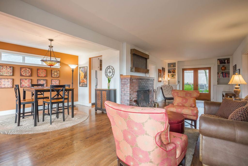 A dining area is a large nook in a larger living area with a fireplace