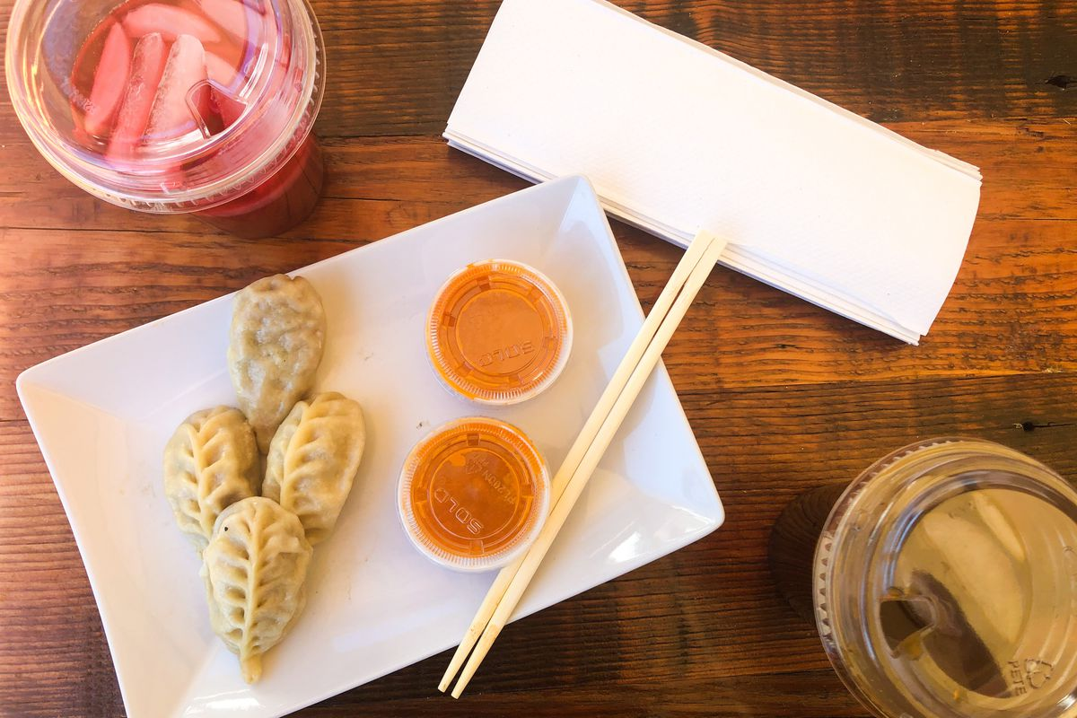 A table with four dumplings on a plate next to two containers of tomato chutney, placed next to hibiscus drinks and Kenyan lemonade