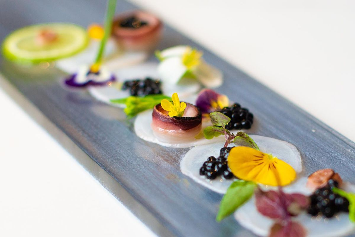 Razor-thin slices of sushi are garnished with flowers and berries